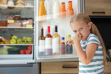 Girl feeling bad smell from stale products in refrigerator at home