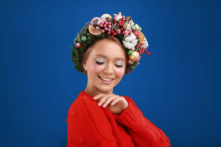 Beautiful young woman wearing Christmas wreath on blue background 스톡 콘텐츠