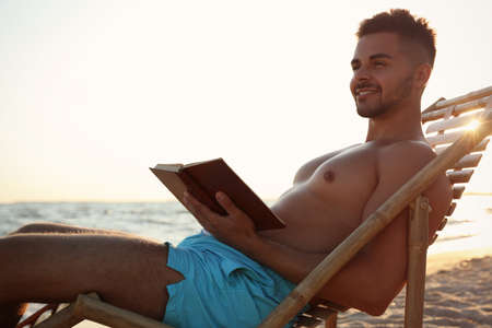 Young man reading book in deck chair on beach