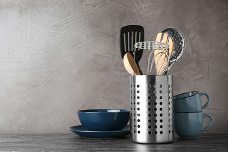 Holder with kitchen utensils on grey table against grey stone background. Space for text Stock Photo