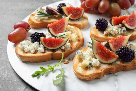 Bruschettas with cheese, figs and blackberries served on table