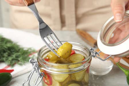 Woman taking pickled cucumber from jar at table, closeup view
