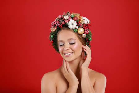 Beautiful young woman wearing Christmas wreath on red background