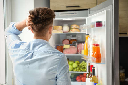 Man looking into refrigerator full of products in kitchen