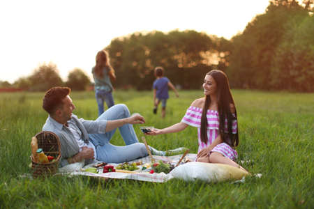 Happy family having picnic in park at sunset