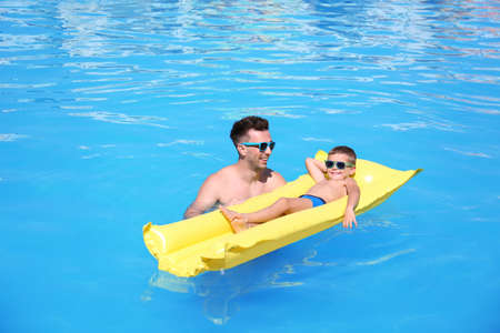 Little boy on inflatable mattress with father in swimming pool