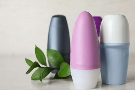 Natural roll-on deodorants and green plant on light grey table