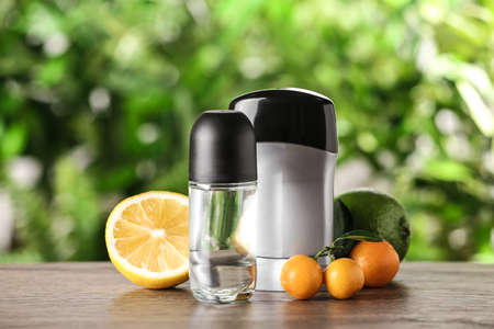 Different deodorants and citrus fruits on wooden table against blurred background 写真素材
