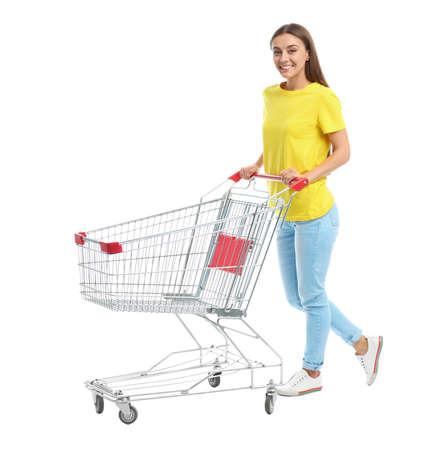Junge Frau mit leerem Einkaufswagen auf weißem Hintergrund