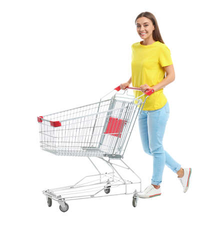 Young woman with empty shopping cart on white background Stok Fotoğraf - 129969913