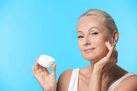 Portrait of beautiful mature woman with perfect skin holding jar of cream on light blue background Reklamní fotografie