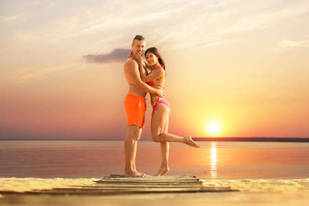 Young woman in bikini spending time with her boyfriend on beach. Lovely couple Reklamní fotografie - 132116164