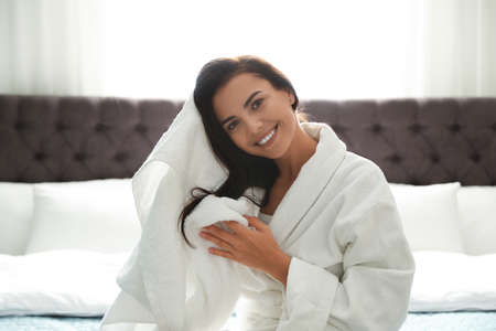 Pretty young woman drying hair with towel on bed in room