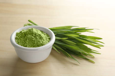 Bowl of wheat grass powder and green sprouts on wooden table