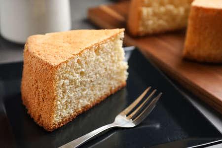 Pedazo de delicioso pastel casero fresco servido en mesa gris Foto de archivo