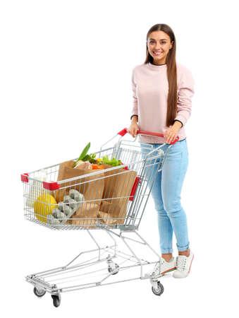 Mujer joven con carrito de compras completo sobre fondo blanco.