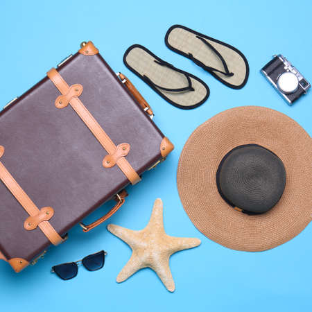 Vintage suitcase and beach objects on blue background, flat lay