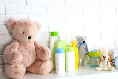 Baby accessories on shelf near white brick wall Reklamní fotografie - 129751475