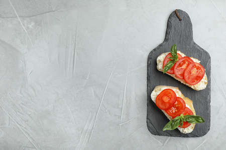 Tasty fresh tomato bruschettas on grey table, flat lay. Space for text