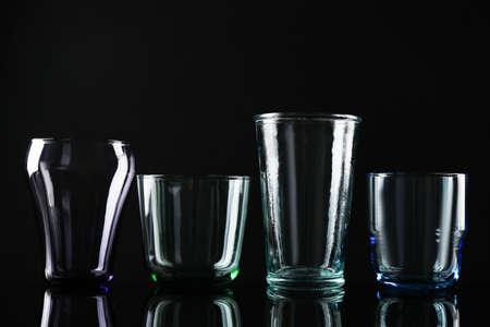 Ensemble de différents verres vides colorés sur fond noir Banque d'images