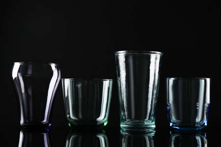 Satz verschiedene bunte leere Gläser auf schwarzem Hintergrund Standard-Bild