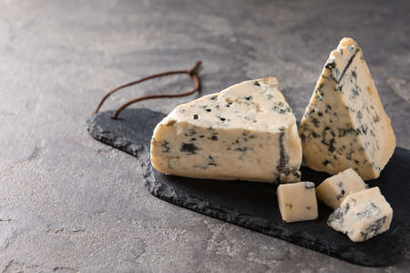 Slate board with delicious blue cheese on stone surface. Space for text