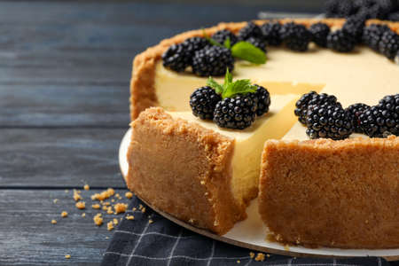 Sliced delicious cheesecake with blackberries on wooden table, closeup