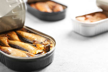 Tin can with sprats on light table, closeup. Space for text