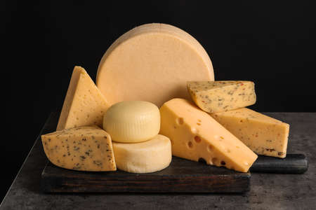 Wooden board with different sorts of cheese on table against black background