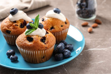 Plate of tasty muffins and blueberries on marble table