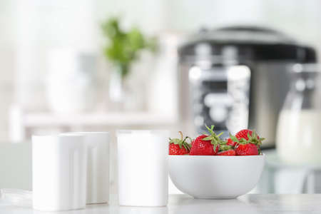 Cups for homemade yogurt and fresh strawberry on table in kitchen. Recipe for multi cooker Фото со стока - 129790402