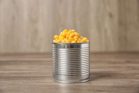 Open tin can of sweet corn on wooden table