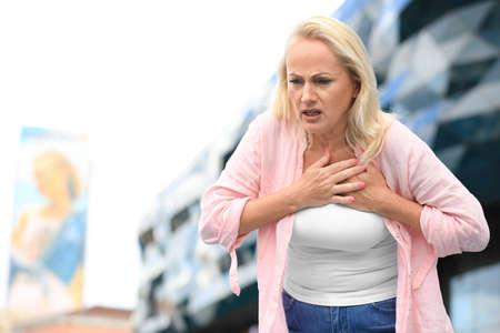 Rijpe vrouw die lijdt aan een hartaanval buitenshuis. Ruimte voor tekst