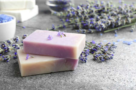 Hand made soap bars with lavender flowers on grey stone table. Space for text