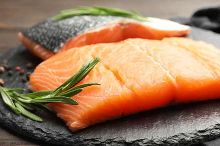 Slate plate with salmon fillet on table, closeup