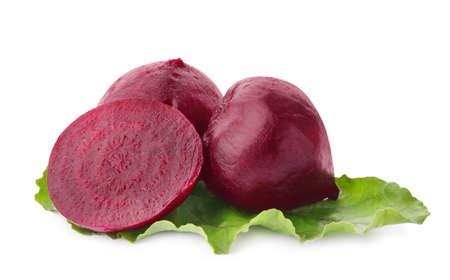 Whole and cut boiled red beets with green leaf on white background