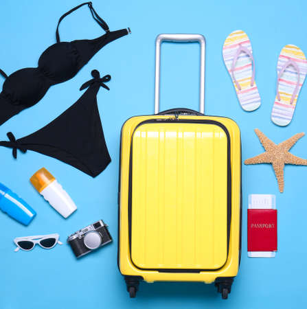 Yellow suitcase and beach objects on blue background, flat lay Reklamní fotografie