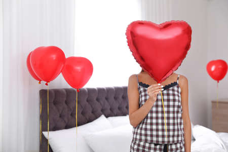 Young woman in bedroom decorated with air balloons. Celebration of Saint Valentines Day