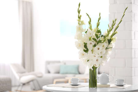 Vase with beautiful white gladiolus flowers on wooden table in living room. Space for text Stock fotó - 129750171