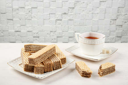 Plate of delicious wafers with cup of tea on white wooden table