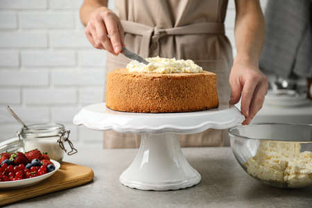Woman decorating delicious cake with fresh cream at table indoors, closeup. Homemade pastry