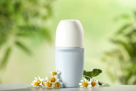 Deodorant container and chamomile on white wooden table against blurred background