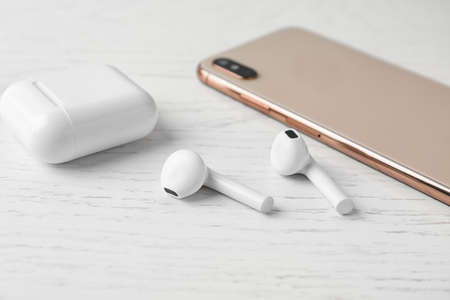 Wireless earphones, mobile phone and charging case on white wooden table Reklamní fotografie