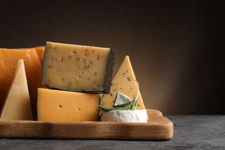 Wooden tray with different sorts of cheese and rosemary on grey table, space for text