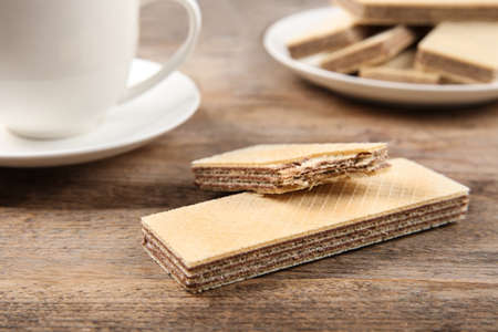 Delicious wafers and cup of drink on brown wooden background, closeup