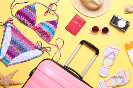 Flat lay composition with suitcase and beach objects on yellow background