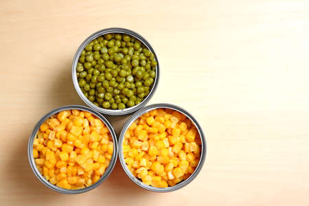 Open tin cans of conserved vegetables on wooden table, flat lay with space for text Stock fotó
