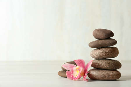 Stack of spa stones and flower on table against white background, space for text