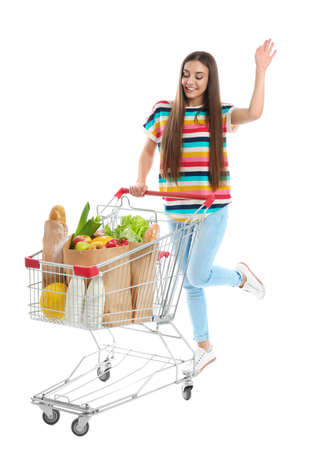 Young woman with full shopping cart on white background Reklamní fotografie