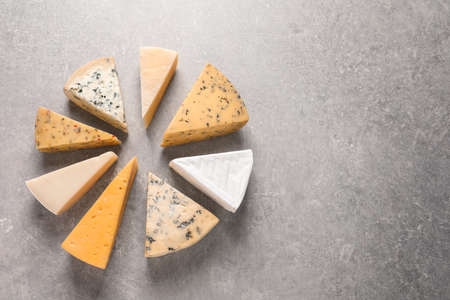 Flat lay composition with different kinds of cheese on grey background, space for text